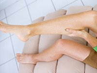 Mujer frotando su pantorrilla, calambres en las piernas