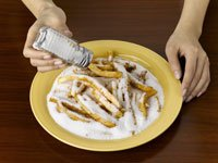 Woman over-salting junk food, We Still Consume Too Much Sodium
