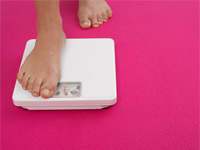 Woman stepping onto weighing scale, Postmenopausal women who lose then regain weight suffer a double-whammy