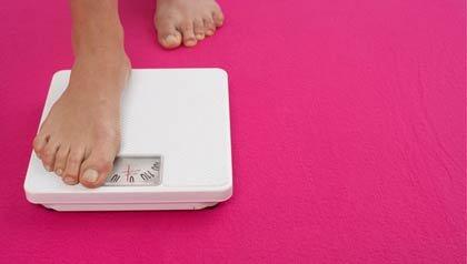 Mujer parándose en una balanza - Recuperar el peso perdido aumenta el riesgo de padecimientos del corazon