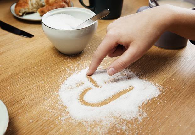 Mujer dibujando un corazón en azúcar sobre una mesa - Alimentos que afectan la salud del corazon