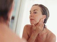 Mujer mirándose la cara en un espejo - Trivia - Como cuidar la piel