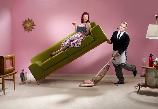 Man sweeping and lifting couch with woman, Spring cleaning