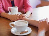 Dos mujeres tomadas de la mano sentadas una frente a la otra - Palabras de consuelo para un amigo enfermo
