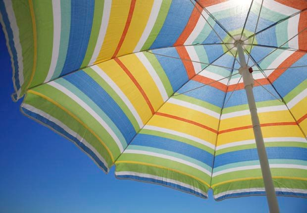 Striped umbrella against blue sky. Carry a parasol to protect yourself from the sun. (Gabor Izso/Istockphoto)