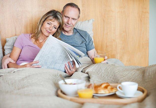 Pareja leyendo el periódico y tomando el desayuno en la cama - 7 cosas que usted puede hacer en el dormitorio que pueden salvar su vida