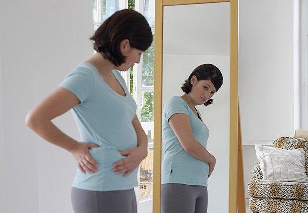 Mujer que mira su cuerpo en el espejo - 7 cosas que usted puede hacer en el dormitorio que pueden salvar su vida