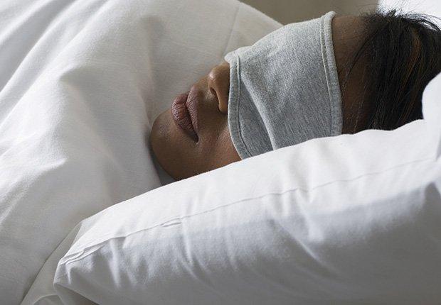 Mujer joven que duerme con la máscara de ojo - 7 cosas que usted puede hacer en el dormitorio que pueden salvar su vida