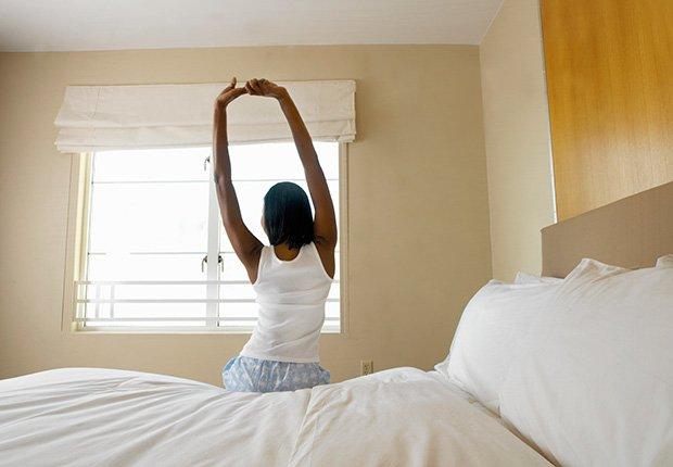 Mujer sentada en el borde de la cama, que hace estiramiento - 7 cosas que usted puede hacer en el dormitorio que pueden salvar su vida