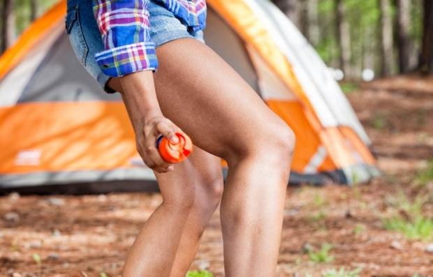 Mujer se aplica repelente de insectos - Cómo prevenir picadas de mosquitos, hormigas y garrapatas durante el verano - Prevenir enfermedades