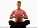 Mujer sentada en posición Namaste en ejercicio tatami con los ojos cerrados - Beneficios del yoga para adultos mayores