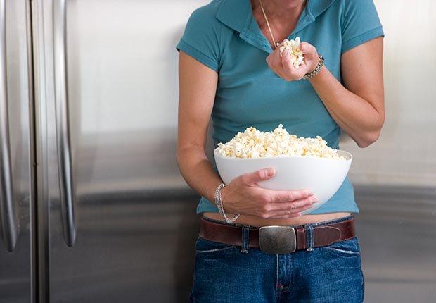 Mujer que come palomitas de maíz, los alimentos diarios con beneficios para la salud