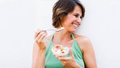 Mujer comiendo yogur - Beneficios y desventajas para su salud de los alimentos probióticos
