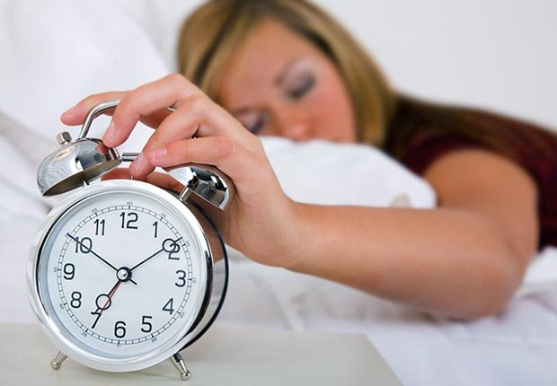 Mujer en la cama que apaga el reloj de alarma - Cuando los buenos hábitos se tornan en malos hábitos