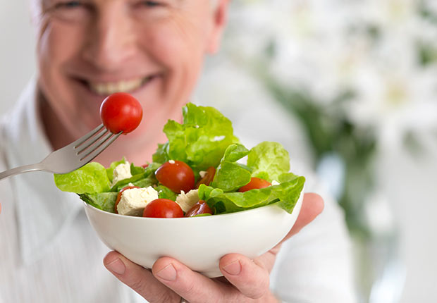 Happy mature man eating salad, when good habits go bad