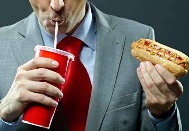 Hombre comiendo un perro caliente - Alimentos y hábitos que nos hacen envejecer