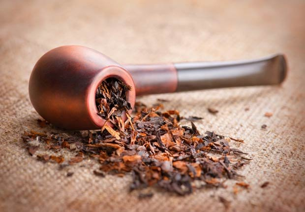 Smoking pipe and tobacco on linen canvas background