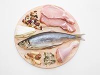 Bandeja con varios trozos de carnes, pescado, queso, granos y nueces - El consumo de proteína de origen animal y el desarrollo de cáncer