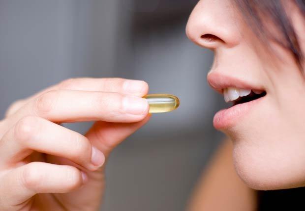 Mujer tomando una vitamina - Mitos sobre las vitaminas