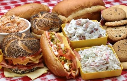 Un almuerzo tipo picnic con sandwiches, ensalada de papas, ensalada de col y las galletas - Prevenir intoxicacion por alimentos