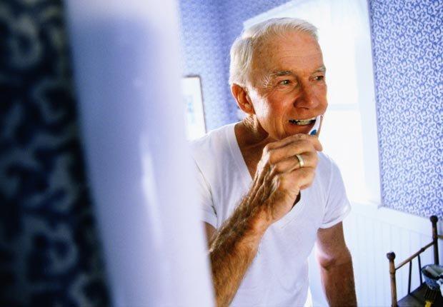 Hombre mayor cepillándose los dientes - Su cepillo de dientes en un semillero para las bacterias?