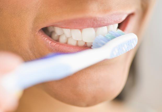 Primer plano de una mujer cepillándose los dientes - Su cepillo de dientes en un semillero para las bacterias?