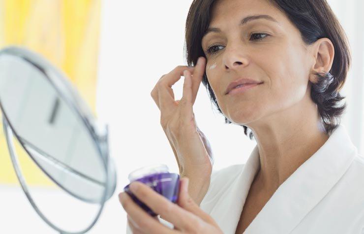 Mujer aplicándose una crema en la cara - Alimentos que protegen tu piel