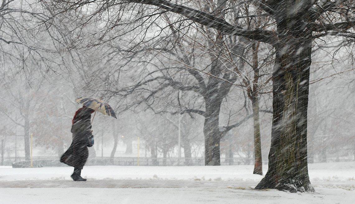 Persona caminando bajo una tormenta de nieve