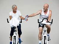 Pareja corriendo bicicleta estacionaria - Beneficios del ejercicios de alto impacto
