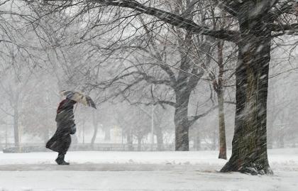 Persona con una sombrilla caminando bajo la nieve - Evite accidentes en invierno - Consejos para mantenerse saludable