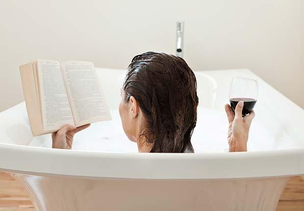 Mujer tomando un baño mientras lee y toma vino - Evita aumentar de peso en Navidad