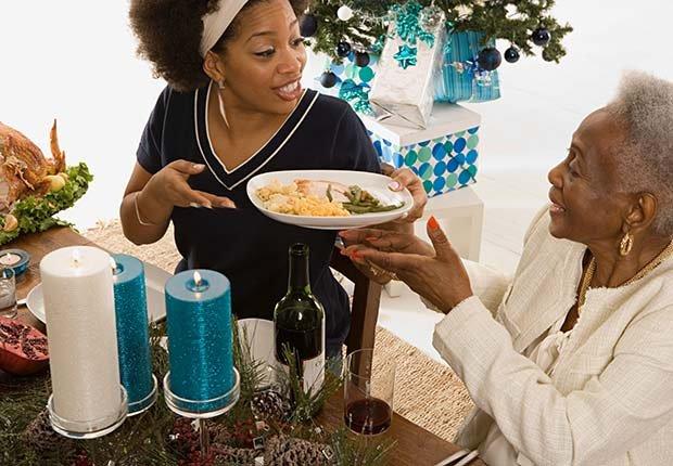 Persona ofreciendo comida a otra - Evita aumentar de peso en Navidad