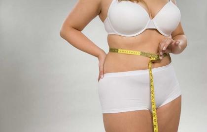 Mujer midiéndose la cintura - Números que pueden extender tu vida