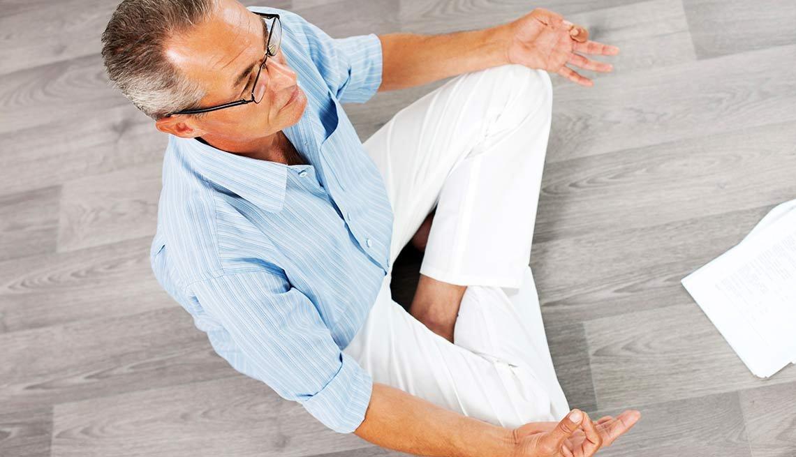 Hombre sentado meditando - Beneficios de la meditación