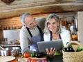 Pareja cocinando y mirando una tableta -  Cómo comer saludable y perder peso