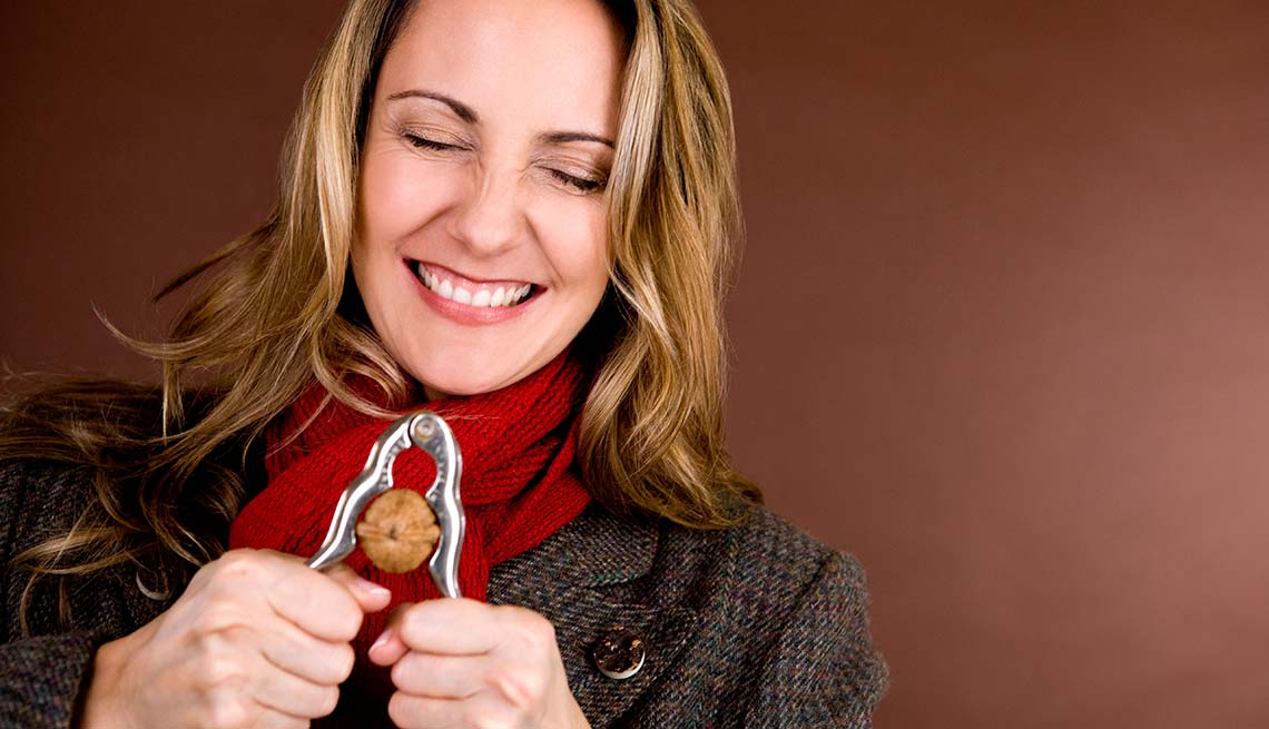 Woman closes her eyes cracking a walnut, Best Nuts Health