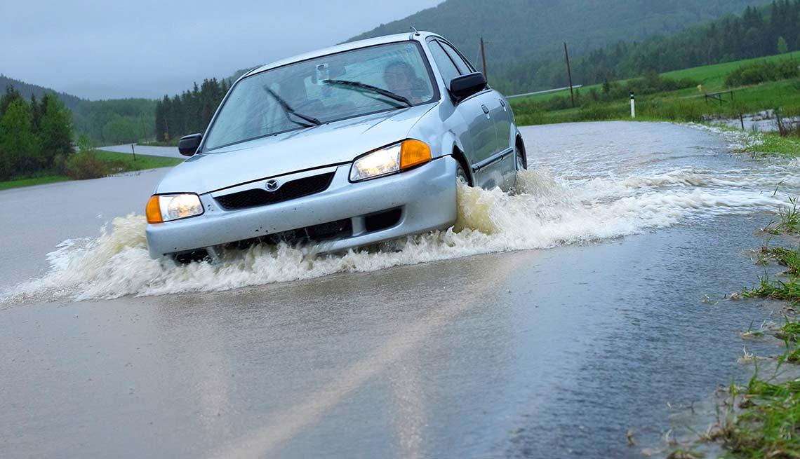 Carro atascando en un hoyo durante una aguacero