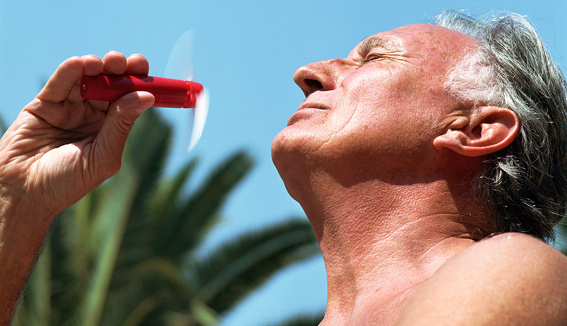 Man with portable fan in the sun, Summer Survival Guide, Heat Exhaustion