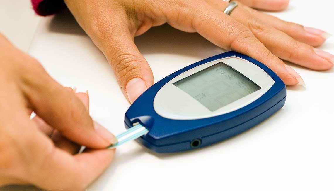 Mujer haciendo una prueba de nivel de azúcar -  Síntomas de la falta de carbohidratos en la dieta
