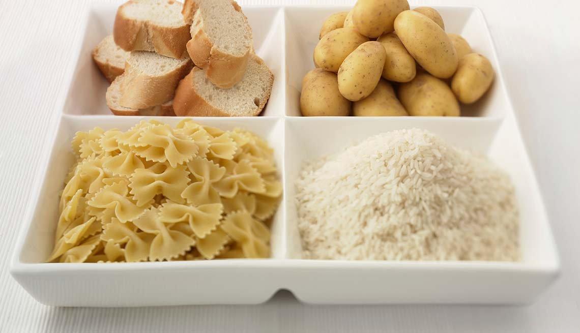 Plato de comida con 4 divisiones con pan, arroz, pan y pastas - Síntomas de la falta de carbohidratos en la dieta