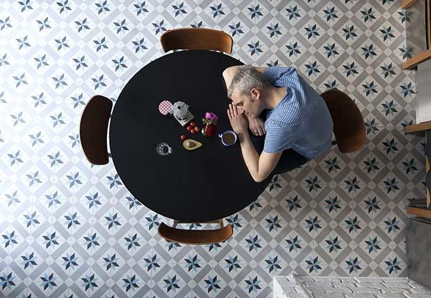 Hombre durmiendo con los brazos apoyados en una mesa - Fatiga - Síntomas de la falta de carbohidratos en la dieta