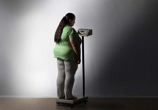 Mujer con sobrepeso en una pesa - Síntomas de la falta de carbohidratos en la dieta