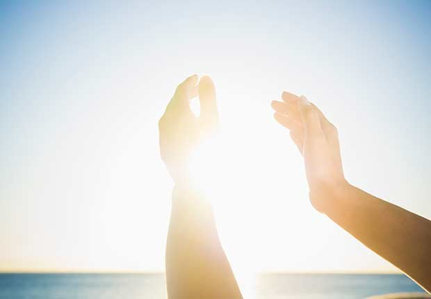Manos intentando agarrar el sol