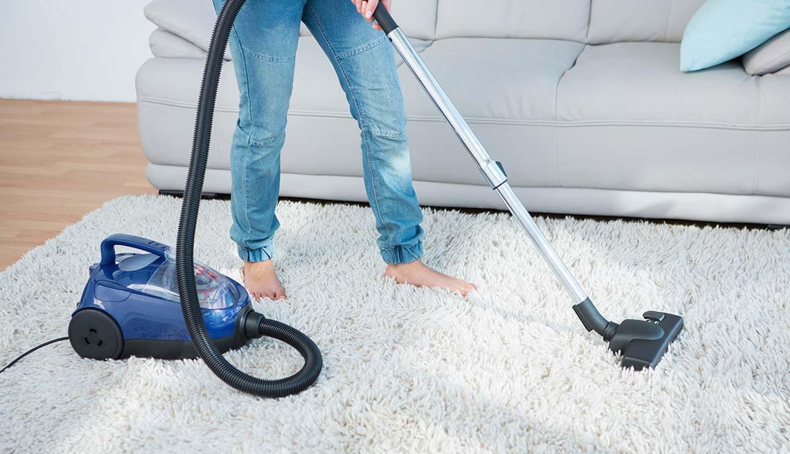 Mujer limpiando con una aspiradora