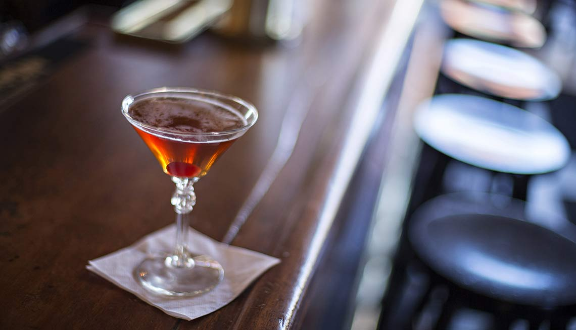 Manhattan in a stemmed glass on a wooden bar, Heart Attack Triggers