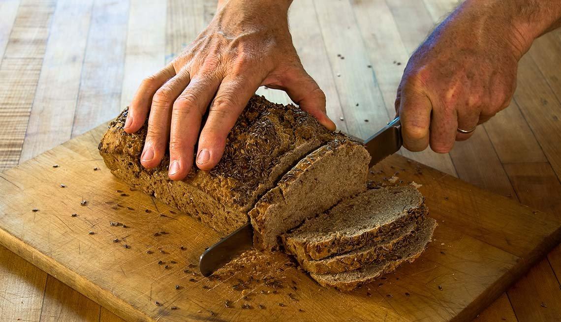 Persona rebanando un pan