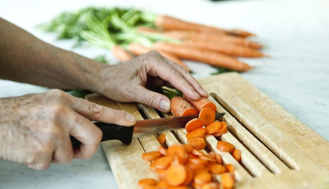 item 4 of Gallery image - Persona rebanando zanahorias
