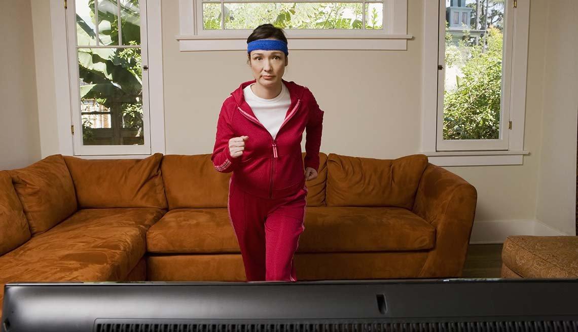 Mujer haciendo ejercicios frente al televisor