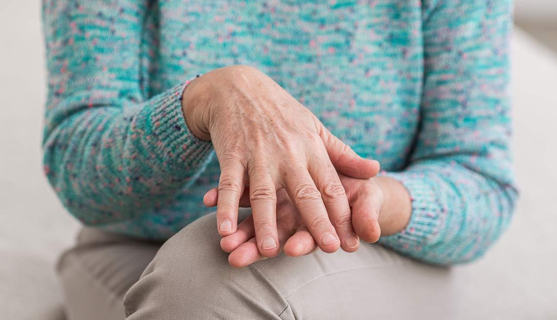 Mujer sentada con sus manos juntas sobre sus piernas cruzadas
