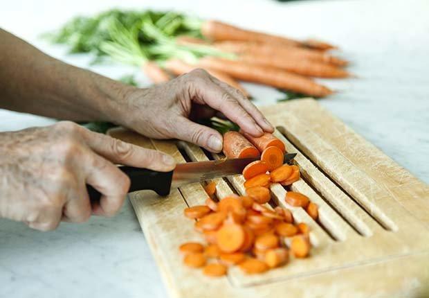 Persona rebanando zanahorias